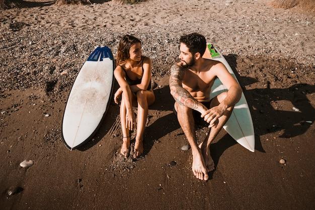 Jovem perto de pranchas de surf e mulher na praia
