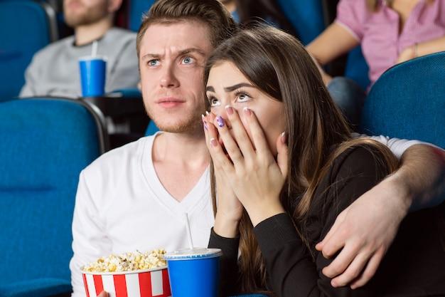 Jovem perturbado, abraçando a namorada assustada enquanto assiste a filmes no cinema