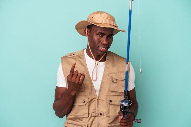 Jovem pescador afro-americano segurando a haste isolada no fundo azul, apontando com o dedo para você como se fosse um convite para se aproximar.