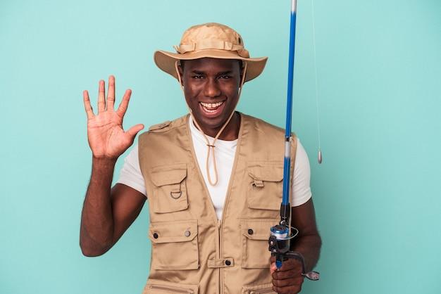 Jovem pescador afro-americano segurando a haste isolada no fundo azul, sorrindo alegre mostrando o número cinco com os dedos.