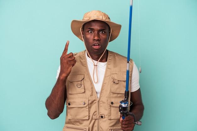Jovem pescador afro-americano segurando a haste isolada no fundo azul, tendo uma ótima ideia, o conceito de criatividade.