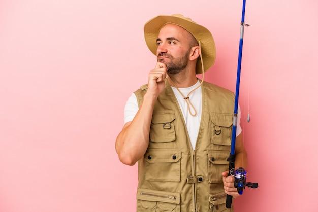 Jovem pescador careca segurando uma vara isolada no fundo rosa, olhando de soslaio com expressão duvidosa e cética.