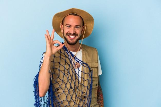 Jovem pescador caucasiano com tatuagens segurando a rede isolada no fundo azul alegre e confiante mostrando o gesto ok.