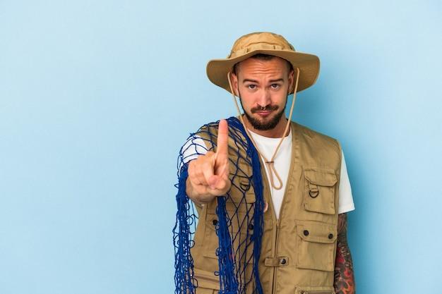 Jovem pescador caucasiano com tatuagens, segurando a rede isolada no fundo azul, mostrando o número um com o dedo.