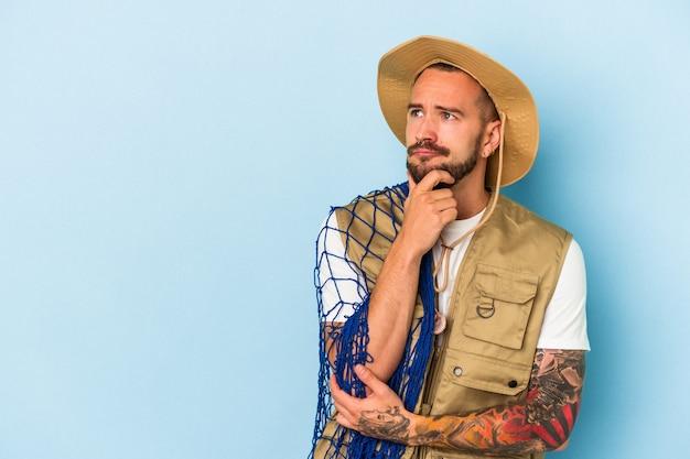 Jovem pescador caucasiano com tatuagens segurando a rede isolada no fundo azul, olhando de soslaio com expressão duvidosa e cética.