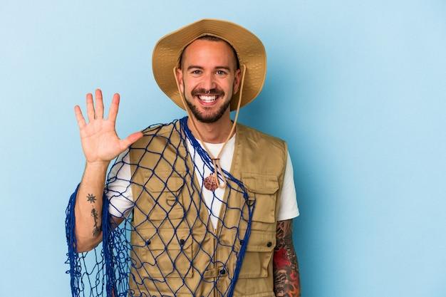 Jovem pescador caucasiano com tatuagens segurando a rede isolada no fundo azul, sorrindo alegre mostrando o número cinco com os dedos.