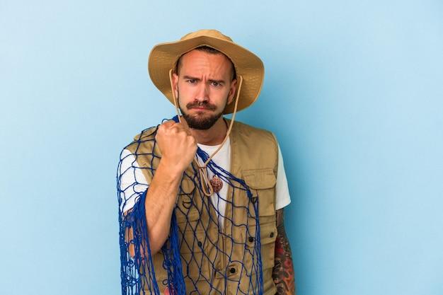 Jovem pescador caucasiano com tatuagens segurando rede isolada em fundo azul, mostrando o punho para a câmera, expressão facial agressiva.
