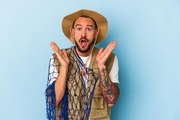 Jovem pescador caucasiano com tatuagens segurando rede isolada em fundo azul surpreso e chocado.