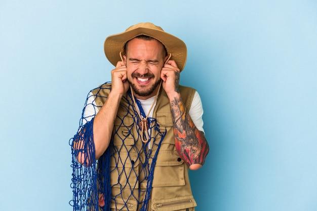 Jovem pescador caucasiano com tatuagens segurando uma rede isolada em um fundo azul, cobrindo as orelhas com as mãos.