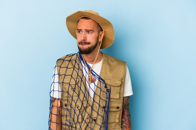 Jovem pescador caucasiano com tatuagens segurando uma rede isolada em um fundo azul confuso, sente-se em dúvida e inseguro.