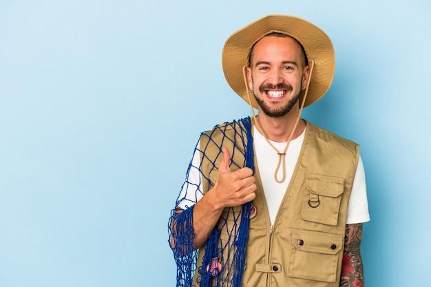 Jovem pescador caucasiano com tatuagens segurando uma rede isolada no fundo azul, sorrindo e levantando o polegar