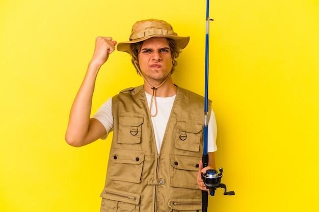 Jovem pescador com maquiagem segurando haste isolada em fundo amarelo, mostrando o punho para a câmera, expressão facial agressiva.