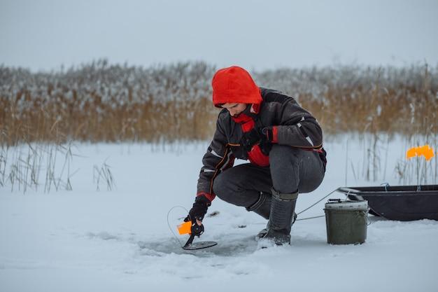 Jovem pescador em um lago de neve no inverno colocando isca