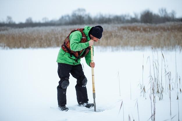 Jovem pescador fazendo um buraco em um lago nevado