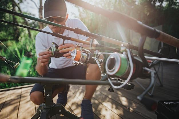 Jovem pescador pescando no lago ou rio. sentado em varas de pesca e ajustando-as antes de começar a colocar iscas e molinetes na água. trabalhando sozinho na natureza.