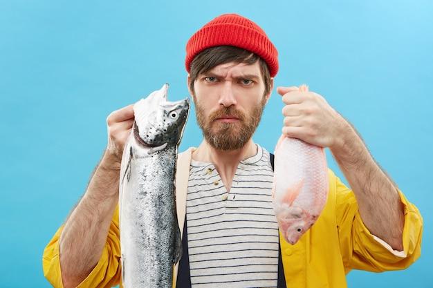 Jovem pescador sério com barba segurando dois peixes de água doce com as duas mãos