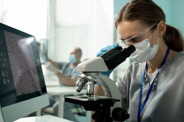Jovem pesquisador de laboratório concentrado com óculos e máscara sentado em frente ao monitor do computador e analisando a amostra através do microscópio