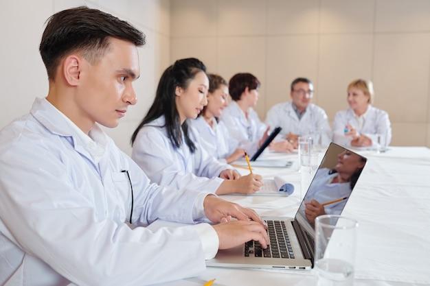 Jovem pesquisador sério trabalhando em um laptop em uma reunião com cientistas dedicados a novos testes de vacinas contra o coronavírus