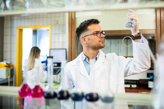Jovem pesquisadora verificando tubos de ensaio em laboratório