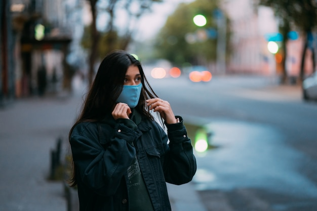 Jovem, pessoa em máscara protetora estéril médica na rua vazia