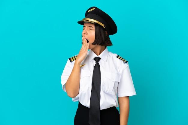 Jovem piloto de avião sobre fundo azul isolado bocejando e cobrindo a boca aberta com a mão