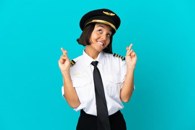 Jovem piloto de avião sobre fundo azul isolado com dedos se cruzando e desejando o melhor