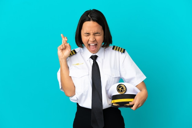 Jovem piloto de avião sobre fundo azul isolado cruzando os dedos