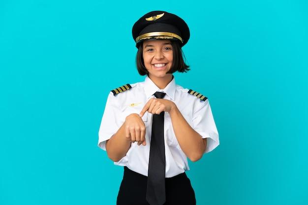 Jovem piloto de avião sobre fundo azul isolado fazendo o gesto de se atrasar