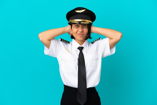 Jovem piloto de avião sobre fundo azul isolado frustrado e cobrindo as orelhas
