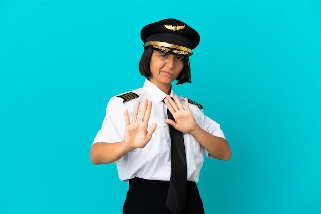 Jovem piloto de avião sobre fundo azul isolado nervoso, estendendo as mãos para a frente