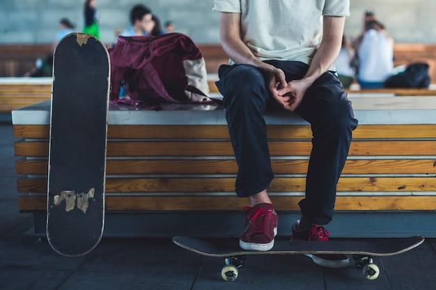 Jovem piloto de skate clássico fechar refrigeração no estilo de vida na rua.