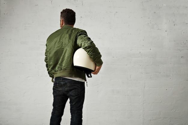 Jovem piloto em jeans, jaqueta verde e um capacete branco redondo debaixo do braço, retrato da parte de trás na parede branca