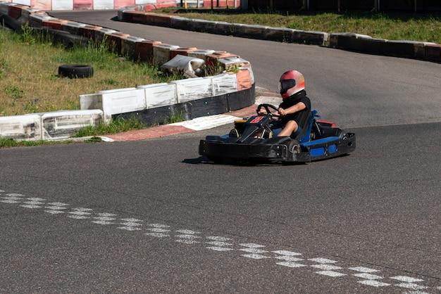 Jovem piloto no campeonato do circuito de corrida de kart cruzando a linha de chegada.