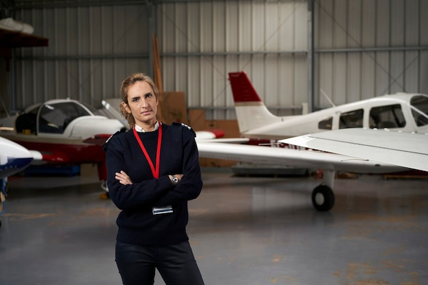 Jovem piloto posando no hangar cercado por aviões