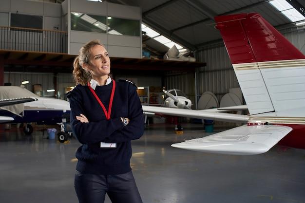 Jovem piloto posando sorrindo no hangar cercado por aviões