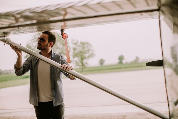 Jovem piloto verificando o avião no hangar