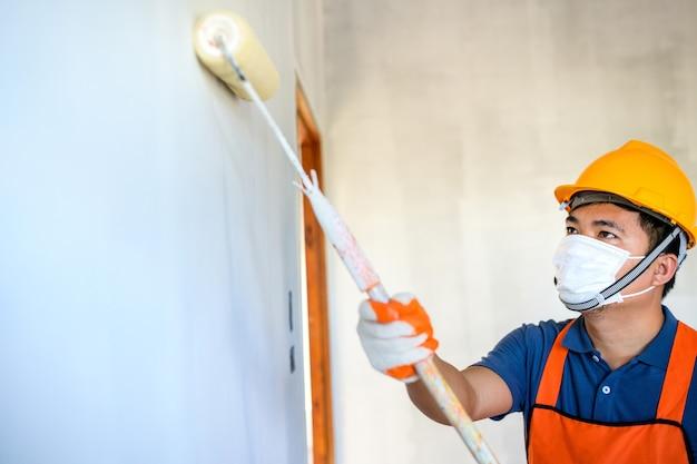 Jovem pintor asiático use uma máscara protetora para pintar as paredes internas de branco com um rolo de pintura na nova casa.