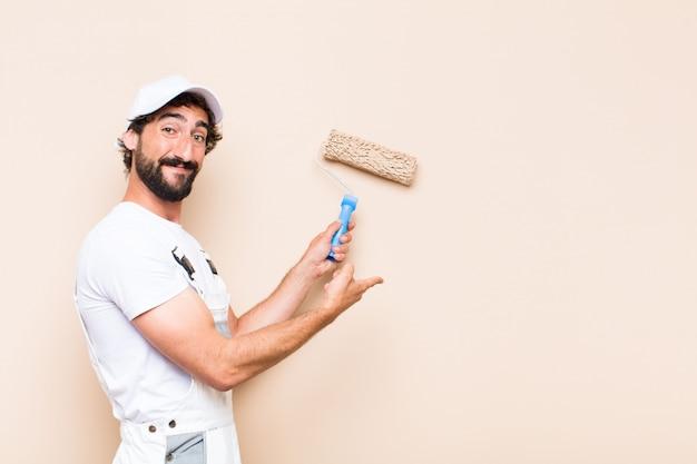Jovem pintor barbudo pintando uma parede com rolo de pintura