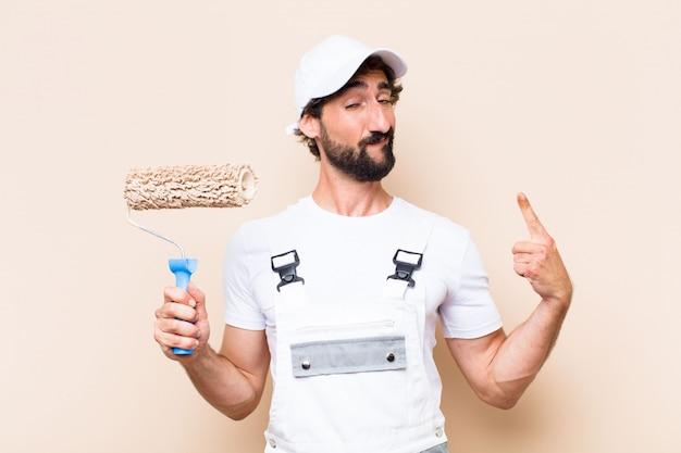 Jovem pintor barbudo segurando um rolo e expressão de orgulho