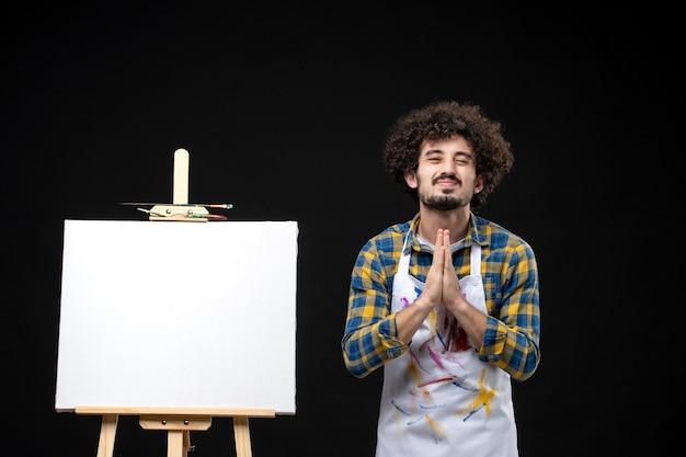 Jovem pintor masculino com cavalete implorando na mesa preta