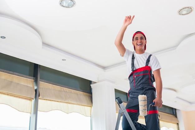 Jovem pintor pintando o teto no conceito de construção