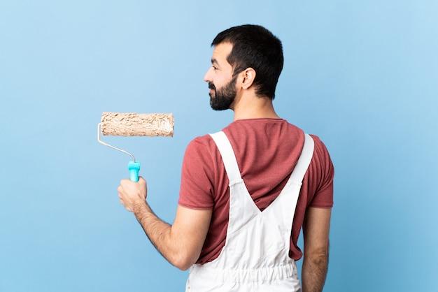 Jovem pintor sobre fundo azul isolado