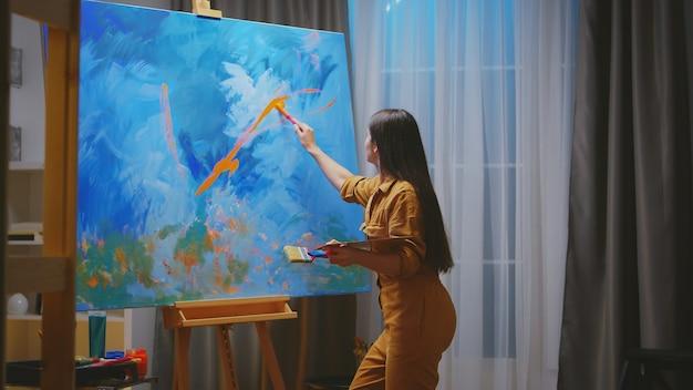 Jovem pintor talentoso usando cores diferentes na tela.