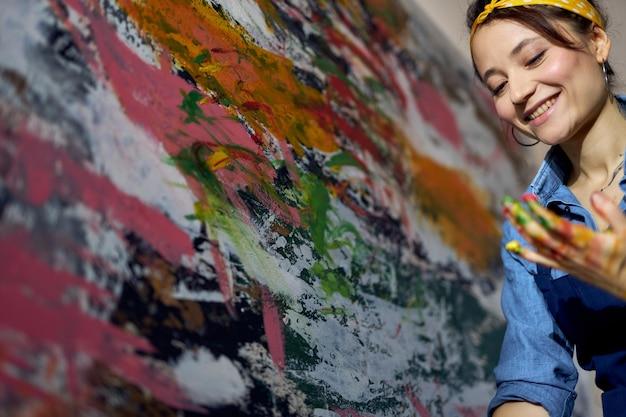 Jovem pintora alegre criando uma grande pintura a óleo abstrata moderna aplicando tinta