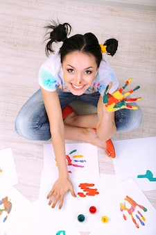 Jovem pintora bonita com as mãos pintadas, em fundo cinza