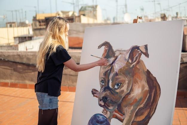 Jovem pintora desenhando no telhado de casa. imagem de bulldog em uma tela grande. arte ao ar livre