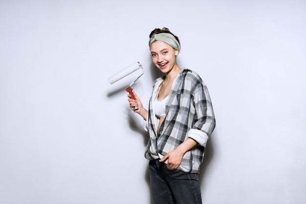 Jovem pintora feliz segurando um rolo para pintar as paredes de seu novo apartamento