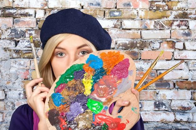 Jovem pintora segurando uma paleta e pincéis com uma parede de tijolos vermelhos no fundo