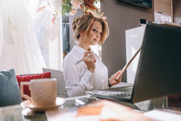 Jovem planejadora de casamento no escritório com laptop e tablet para escrever