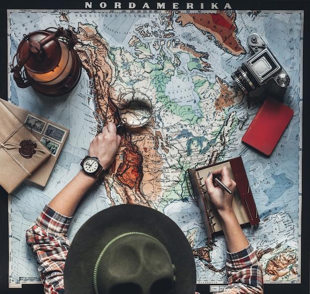 Jovem planejando férias usando o mapa do mundo outros acessórios de viagem.